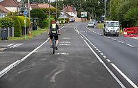 BNPS.co.uk (01202) 558833. <br /> Pic: CorinMesser/BNPS<br /> <br /> Pictured: One of only two cyclists spotted riding along the cycle lane in a two hour period on Monday (16/08/21) afternoon. <br /> <br /> A cycle lane which is believed to be one of Britain's widest has been slammed by road users who are bemused by its size.<br /> <br /> Despite measuring over half as wide as the adjacent road, cyclists have still been spotted using the carriageway instead of the cycle lane.<br /> <br /> The cycle way is a whopping 11ft wide, 2ft wider than the vehicle lane which locals say is frequented by heavy goods and emergency vehicles.<br /> <br /> Residents on Wimborne Road West in Wimborne, Dorset, were exasperated when they woke one morning to the 'cycle highway' as it has been dubbed by the local council.<br /> <br /> It is part of a major £102 million scheme to make travel more sustainable and reduce congestion across the county but they argue it could have the opposite effect by obstructing traffic.