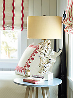 A lamp with a shell base sits on a blue topped table bedside a bed.