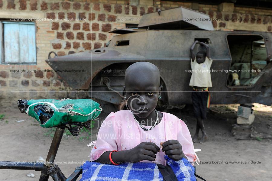 SOUTH SUDAN, Bahr al Ghazal region, Lakes State, town Rumbek , Dinka girl at old battle tank from war between SPLA and north sudanese army / SUED-SUDAN  Bahr el Ghazal region , Lakes State, Rumbek , Dinka Maedchen am Wrack eines nordsudanesischen Schuetzenpanzers aus dem Buergerkrieg mit dem Sudan an der Rumbek Secondary School