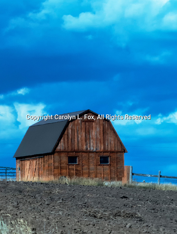 An old barn sits on a hill against a bright blue sky.