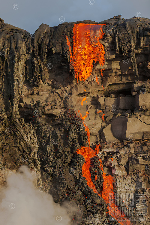 Lava drips off of a cliff into the ocean near Kalapana on the Big Island of Hawai'i.