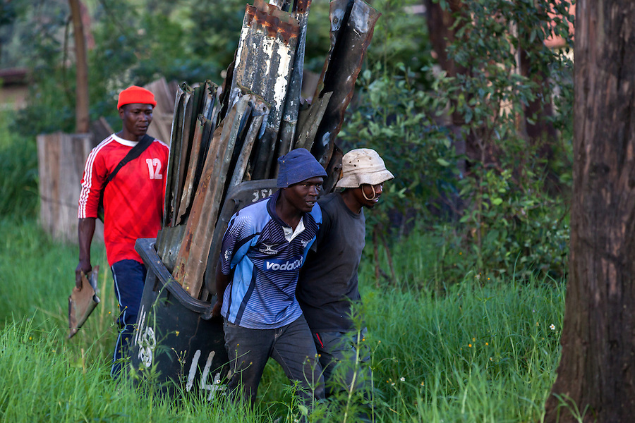 Men carry metal stripped from one of Durban Deep gold mine's homes on the outskirts of Johannesburg, South Africa. The metal is sold to local scrapyards and while it isn't as valuable as copper, for the many unemployed men in the area, it provides some cash.
