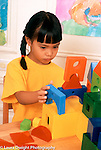 4 year old girl building with colored wooden blocks closeup vertical