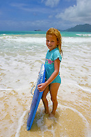 A red-headed girl holds her boogieboard on Bellow's Beach ready to play in the gentle surf.