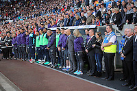 The Swansea bench with Swansea manager Bob Bradley (C) observe a minute's silence for the 50th anniversary pf the Aberfan disasterprior to the Premier League match between Swansea City and Watford at The Liberty Stadium on October 22, 2016 in Swansea, Wales, UK.