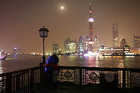 CHINA. Shanghai. A young couple on the Bund with the famous Pudong skyline behind them. Shanghai is a sprawling metropolis or 15 million people situated in south-east China. It is regarded as the country's showcase in development and modernity in modern China. This rapid development and modernization, never seen before on such a scale has however spawned countless environmental and social problems. 2008.