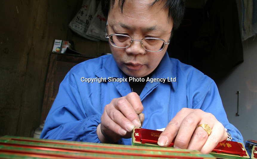 A worker checks and adjust the tone of harmonicas at the Shanghai General Harmonica Factory (SGHF) in Shanghai, China. Although it makes well-respected brands such as the Huang, Suzuki, and Hohner that are favored by many professional musicians around the world, the 60 years old state owned SGHF had to trim down its work force from 800 in the mid 1980's to just over 100 today..23-FEB-04