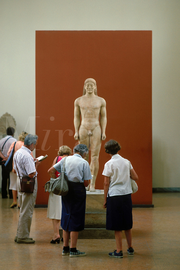 "Dating from approximately 600 B. C., this stone sculpture is a """"kouros,"""" a votive statue of a young man standing or walking, representing the idea of youth, health, and vigor. This Kouros was found in a cemetery near Athens. 1.94 meters tall.  National Mu"