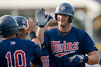 Michael Gonzales #32 of the Elizabethton Twins is congratulated by his teammates at home plate following his 3rd inning grand slam at Burlington Athletic Park July 19, 2009 in Burlington, North Carolina. (Photo by Brian Westerholt / Four Seam Images)