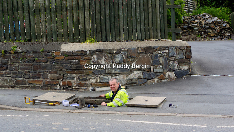 A repairman half submerged in a manhole to install and repair telephone wires.<br />