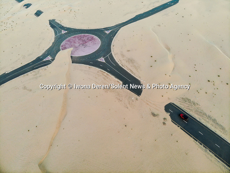 "Pictured: Desert roads lie almost completely hidden - as aerial images show them being swallowed up wind-blown sand.   Just a single car can be seen trying to cross the tarmac near Dubai as the surrounding dunes threaten to cover them up entirely.<br /> <br /> The striking photos were captured by Polish airline worker Iwona Deren who had travelled to the United Arab Emirates to practice off road driving in the desert.   ""Pretty much all roads in the UAE, especially those in the middle of the desert need to be maintained constantly to remove the sand blowing from the dunes nearby,"" the 30 year old said.   SEE OUR COPY FOR DETAILS<br /> <br /> Please byline: Iwona Deren/Solent News<br /> <br /> © Iwona Deren/Solent News & Photo Agency<br /> UK +44 (0) 2380 458800"