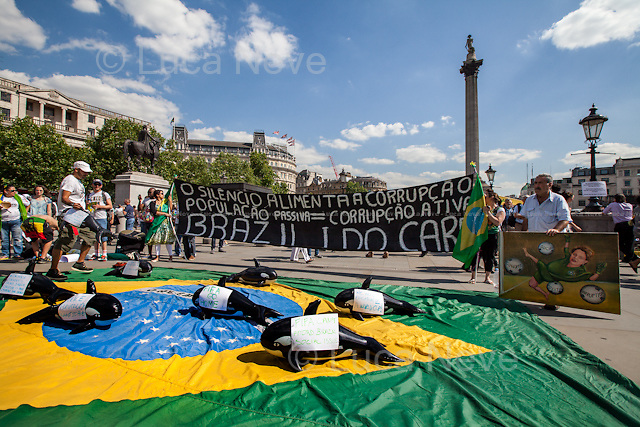 """""""O Silencio Alimenta A Corrupcao. Populacao Passiva = Corrupcao Ativa. Brazil I Do Care"""".<br /> <br /> Kaya Mar (Painter and political caricaturist).<br /> <br /> London, 12/06/2014. Today, on the day of the opening ceremony of the 20th World Cup of Football in Sao Paolo (Brasil), a group of Brasilian people held a demonstration in Trafalgar Square to raise awareness of the problems that are still affecting their country (see photo captions) and in support and solidarity with the protests currently happening in Brasil. Meanwhile, the official """"Brazil Day"""" organised by the Mayor of London was held without disruption in the main square."""