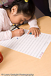 Education Preschool 3-4 year olds girl writing name on class sign-in sheet vertical