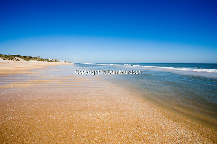 Beautiful shell colored beach and bright blue skies.