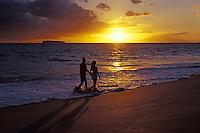 A couple walks at the water's edge enjoying a Maui sunset at Big Beach, Makena, Maui.