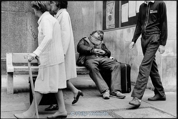 Homeless man sleeping on a bench, King's Cross, London 1990.