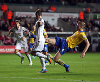 Saturday 28 September 2013<br /> Pictured: Ben Davies of Swansea (L) has the ball slightly deflected temporarily by Per Mertesacker of Arsenal (R) but manages to score a goal.<br /> Re: Barclay's Premier League, Swansea City FC v Arsenal at the Liberty Stadium, south Wales.