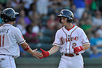 Center fielder Andrew Benintendi (2) of the Greenville Drive is congratulated as he crosses the plate in a game against the Greensboro Grasshoppers on Wednesday, August 26, 2015, at Fluor Field at the West End in Greenville, South Carolina. Benintendi is a first-round pick of the Boston Red Sox in the 2015 First-Year Player Draft out of the University of Arkansas. Greenville won, 7-0. (Tom Priddy/Four Seam Images)