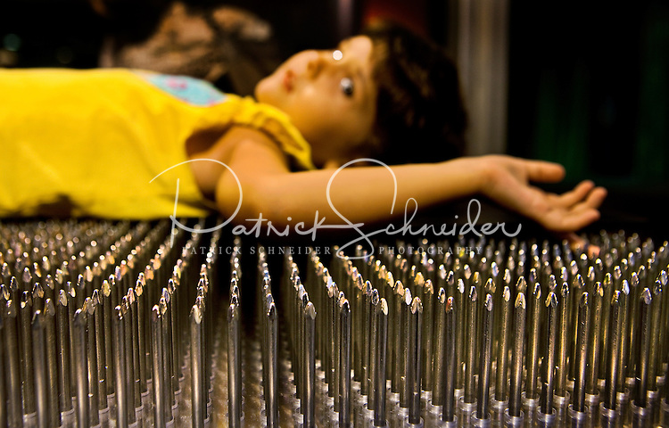 """Visitors to Charlotte's Discovery Place museum check out Kid Science, an interactive hands-on learning lab created to inspire inquiry-based  learning. Here, a child tries out a """"bed of nails."""" Discovery Place, Charlotte NC's interactive children's museum, unveiled its interactive exhibits and hands-on activities in June 2010. Renovations of the popular family museum were made possible by the City of Charlotte, the Arts and Science Council and private donations. Discovery Place museum has age-appropriate exhibits for kids of all ages."""