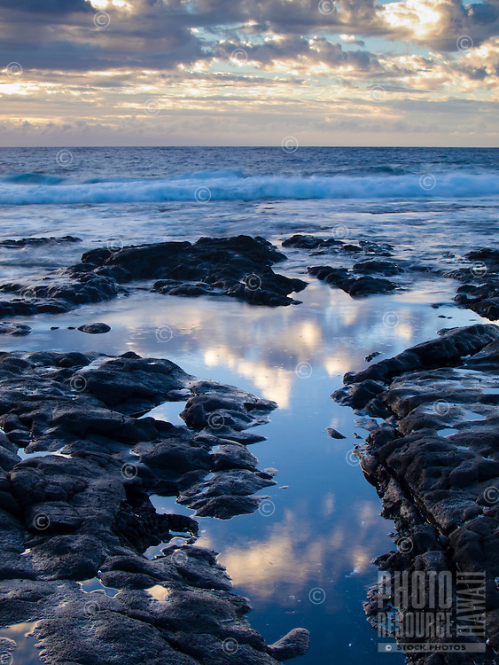 Reflections of the clouds at sunset in tide pools along the rocky shoreline of Keahole Point, Big Island.