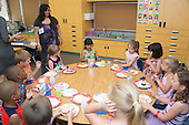 MR / Schenectady, NY. Zoller Elementary School (urban public school). Kindergarten classroom. Mother (Caribbean American) at student's classroom birthday party with cupcakes. MR: AM-gKw. ID: AM-gKw. © Ellen B. Senisi.
