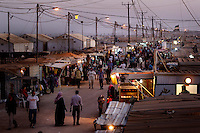People walk through a busy night market set up in the Zaatari Refugee Camp. Approximately two million people have fled the conflict in Syria. At least 130,000 of them live in Zaatari Refugee Camp, although it was designed to house 60,000, and a further 2,000 people arrive each day.