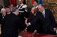 Il Ministro della Difesa Mario Mauro stringe la mano al Presidente del Consiglio Enrico Letta, destra, affiancato dal Presidente della Repubblica Giorgio Napolitano, al centro, alla cerimonia del giuramento del nuovo governo al Quirinale, Roma, 28 aprile 2013..Italian Defense Minister Mario Mauro shakes hands with Premier Enrico Letta, right, past Head of State Giorgio Napolitano, center, during the swearing in ceremony of the new government at the Quirinale presidential palace Rome, 28 April 2013..UPDATE IMAGES PRESS/Isabella Bonotto