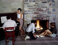 Couples lighting a fire & one couple by the piano in the lodge lobby.