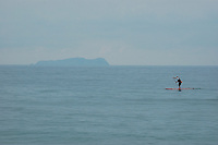 """Isla Los Coronados, Mexico are visible to the South as Tom Jones approaches the US Mexico border at Border Field State Park, the south-western most corner of the contiguous United States, Friday, November 9, 2007.  Jones became the first person to paddle the entire 1250-mile coast of the California on a paddleboard when his three and a half month long journey ended at the border fence in southern San Diego.   The expedition, called """"California Paddle 2007"""" was designed to draw attention to the problem of plastic pollution in the world's oceans and its detrimental effect on marine life.  (Photo Ronan Gray)"""