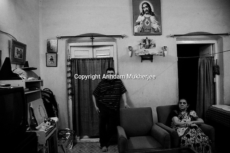 Mrs. Martin with her son at her house in Bow Barracks - one of the oldest Anglo Indian localities where the community has lived since generations. At present, the Bow Barracks residents are at loggerheads with the government and local real estate sharks. With threats of eviction in the air, existence of the Anglo Indians has become tense and tentative.