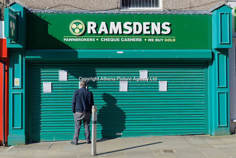 Pictured: A man reads the notices on the shutters of Ramsdens pawn shop in the city centre of Swansea, Wales, UK. Wednesday 25 March 2020 <br /> Re: Covid-19 Coronavirus pandemic, UK.