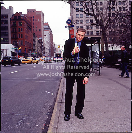 Man in suit standing on sidewalk holding a banana and posturing as an ape