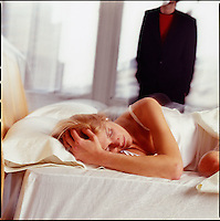 Woman in bed with man in background<br />