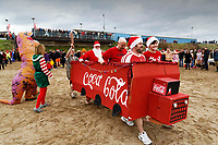 People in Santa fancy dress and a make-shift Coca Cola truck