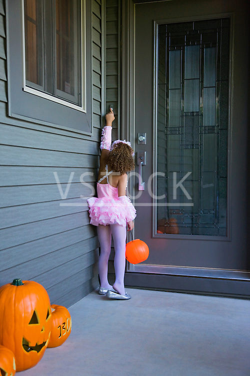 USA, Illinois, Metamora, Girl (6-7) in Halloween costume knocking to doors