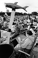 USA. New York. Central Park. An audience estimated at some 200,000 people pack the Great Lawn in Central Park to enjoy a clement summer evening to listen to a musical concert by The New York Philharmonic with Leonard Bernstein as conductor. A woman seats on a camping chair and reads a magazine. An inflatable toy shark on a wooden stake. 5.08.1986 © 1986 Didier Ruef