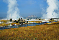 Firehole River with white steam billowing into blue skies at Yellowstone National Park.