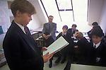 1990s Schoolboy reading out loud his work in classroom, secondary school Amersham Buckinghamshire UK  90s UK. Male man school teacher listening. Boys wearing school uniform, ties, white shirts and dark blazers.  Single sex all only boys school group.