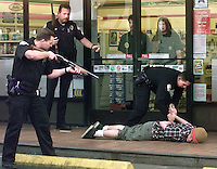 O.gun.0316.jl.photo lytle.Oceanside police Officers handcuff suspect at gunpiont infront of the Seven Eleven on South Coast High Way and Cassidy Monday afternoon after the police recieved 3 911 calls on a subject carring a gun,  wearing a beannie with a red stripe on it in the area. The weapon turned out to be a toy gun and the suspect was reliesed shortly after.