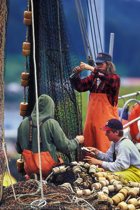 Commercial fishermen mend seine net in Kodiak harbor, Alaska.