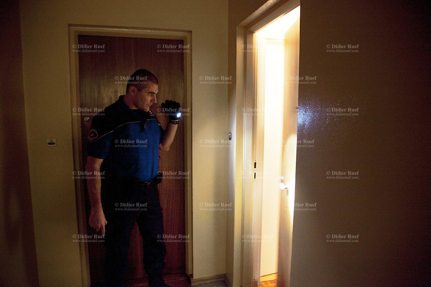 Switzerland. Geneva. Paquis neighborhood. A police officer holding a flashlight in his hands waits for a man to open the door of his flat. The policeman is wearing under his polo shirt a ballistic vest, bulletproof vest or bullet-resistant vest which is an item of personal armor that helps absorb the impact from knives, firearm-fired projectiles and shrapnel from explosions, and is worn on the torso. Soft vests are made from many layers of woven or laminated fibers and can be capable of protecting the wearer from small-caliber handgun and shotgun projectiles. 06.05.12 © 2012 Didier Ruef..
