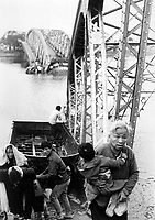 The old and the young flee Tet offensive fighting in Hue, managing to reach the south shore of the Perfume River despite this blown bridge.  1968. (USIA)<br /> EXACT DATE SHOT UNKNOWN<br /> NARA FILE #:  306-MVP-22-9<br /> WAR & CONFLICT BOOK #:  406