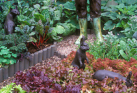Lettuces in red and green, chard, kale, squash in vegetable garden with cute and funny rabbit statue ornaments, fox, gardener's boots