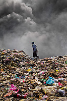 A Nicaraguan man works on the burning pile of garbage in the garbage dump La Chureca, Managua, Nicaragua, 4 November 2004. La Chureca is the biggest garbage dump in Central America. Hundreds of trash recollectors search in tons of smouldering garbage mainly metals (copper, aluminium), others concentrate on glass which is cheap, but in bigger amount. The majority of the recyclers are families with children for whom recycling is a regular job. The children very often eat the food they find on the dump, none of them goes to school, they suffer from skin diseases, they have high levels of lead and DDT in blood.