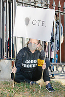 """A crowd gathers in Boston Common for the 2020 Women's March protest in opposition to the re-election of US president Donald Trump in Boston, Massachusetts, on Sat., Oct. 17, 2020.<br /> The sign here features a fly as the first letter in the word """"Vote."""""""