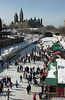 Ottawa, February 24, 2001.Families and week enders skate on the Rideau Canal in downtown Ottawa, CANADA, february 24,2001..We recognize the Parliement Tower as well as  a Canadian Governement Buiding in the background.