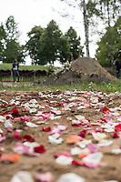"""Das """"Zentrum fuer Politische Schoenheit"""" liess am Dienstag den 16. Juni 2015 auf dem Muslimischen Teil des Friedhof in Berlin-Gatow eine Fluechtlingsfrau aus Syrien beerdigen, die mit ihrem Kind bei der Flucht ueber das Mittelmeer ertrunken ist. Ihr Kind konnte nicht geborgen werden, es ist im Mittelmeer verschollen.<br /> Die Frau wurde zuvor im Beisein von Angehoerigen in Suedeuropa exhumiert und durch ein Beerdigungsunternehmen nach Deutschland gebracht. Die Beerdigung fand unter dem Motto """"Die Toten kommen"""" statt und war die erste von insgesammt 10 geplanten Beerdigungen.<br /> Vor dem Grab waren 40 Stuehle fuer eingeladene Beerdigungs-Gaeste aufgestellt die jedoch leer blieben. Es waren die politisch Verantwortlichen der deutschen Asylpolitik geladen worden, die jedoch nicht erschienen.<br /> Das Zentrum fuer Politische Schoenheit will 8 weitere Mittelmeer-Tote nach Berlin bringen und sie vor das Kanzleramt bringen um den politisch Verantwortlichen die Folgen ihrer Asylpolitik drastisch vor Augen zu fuehren.<br /> Im Bild: Rosen werden auf den Weg den der Sarg der Mutter nehmen wird gestreut.<br /> 16.6.2015, Berlin<br /> Copyright: Christian-Ditsch.de<br /> [Inhaltsveraendernde Manipulation des Fotos nur nach ausdruecklicher Genehmigung des Fotografen. Vereinbarungen ueber Abtretung von Persoenlichkeitsrechten/Model Release der abgebildeten Person/Personen liegen nicht vor. NO MODEL RELEASE! Nur fuer Redaktionelle Zwecke. Don't publish without copyright Christian-Ditsch.de, Veroeffentlichung nur mit Fotografennennung, sowie gegen Honorar, MwSt. und Beleg. Konto: I N G - D i B a, IBAN DE58500105175400192269, BIC INGDDEFFXXX, Kontakt: post@christian-ditsch.de<br /> Bei der Bearbeitung der Dateiinformationen darf die Urheberkennzeichnung in den EXIF- und  IPTC-Daten nicht entfernt werden, diese sind in digitalen Medien nach §95c UrhG rechtlich geschuetzt. Der Urhebervermerk wird gemaess §13 UrhG verlangt.]"""