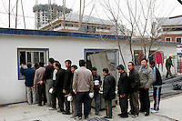 Migrant workers from Sichuan line up and get lunch with a ticket through a window of the kitchen at a construction site in Beijing, China. The meal includes a big bowl of rice and a big bowl of cabbage with pork..