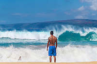 A skimboarder almost completely covered by a wave rides in to shore while a friend watches on a day with unusually large swells at Big Beach in Makena State Park, Maui.
