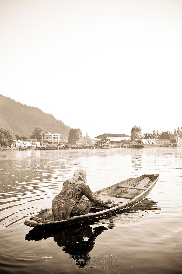 Muslim woman paddling her shikara on Dal Lake, Srinagar, Kashmir, India.